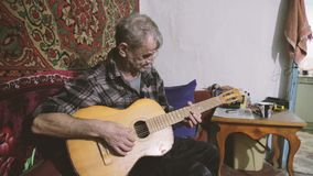 An elderly man plays the guitar, poor grandpa playing the guitar