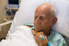 Elderly man. Elderly 80 plus year old man recovering from surgery in a hospital bed Royalty Free Stock Photo