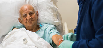 Elderly man. Elderly 80 plus year old man recovering from surgery in a hospital bed Royalty Free Stock Photography