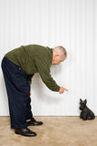 Elderly man pointing at dog ornament Royalty Free Stock Image