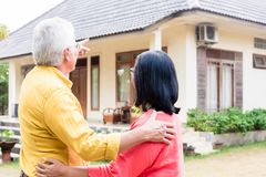 Elderly man pointing to a comfortable residential house while st. Elderly men pointing to a comfortable residential house while standing close to his wife Stock Image