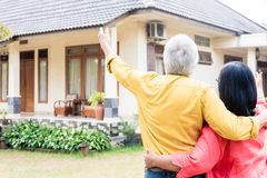 Elderly man pointing to his wife a comfortable residential house. Elderly men pointing to a comfortable residential house while standing close to his wife royalty free stock image