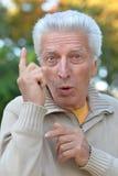 Elderly man pointing up Stock Photo