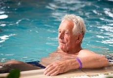 Elderly man in pool stock photography