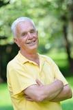 Elderly man portrait. Happy healthy and fit elderly man portrait in green background park stock image