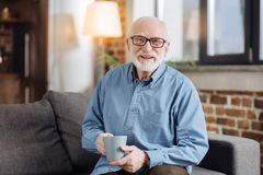 Elderly man posing with a cup of coffee on sofa. Delicious drink. Pleasant elderly man in spectacles sitting on the sofa and posing with a cup of coffee while Stock Image