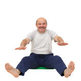 Elderly man practicing yoga or fitness. Stock Photos
