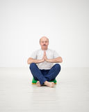 Elderly man practicing yoga or fitness. Positive mood on sports Royalty Free Stock Image