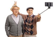 Elderly man pranking another man with bunny ears and taking self Stock Photography