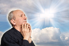 Elderly man praying. On the background of the sky with a cross, a symbol of faith royalty free stock photography