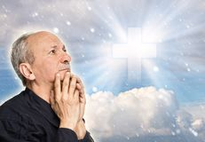Elderly man praying. On the background of the sky with a cross, a symbol of faith and snawfall stock image