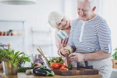 Elderly man preparing vegan salad Royalty Free Stock Photography