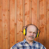 Elderly man in a protective building headphones Stock Images
