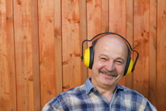 Elderly man in a protective building headphones Stock Photos