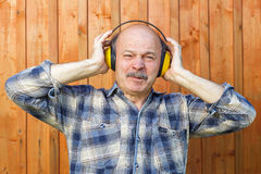 Elderly man in a protective building headphones. Unpleasant soun Royalty Free Stock Image