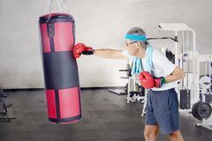 Elderly man punching a boxing bag. Image of an elderly man practicing boxing by punching a boxing bag in the fitness center Royalty Free Stock Photos