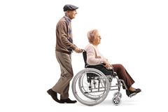 Free Elderly Man Pushing A Disabled Woman In A Wheelchair Royalty Free Stock Photo - 139173975
