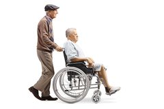 Elderly man pushing a senior male patient in a wheelchair stock image