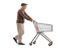 Elderly man pushing a shopping cart Royalty Free Stock Image