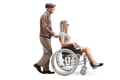 Elderly man pushing a young woman in a wheelchair royalty free stock photos