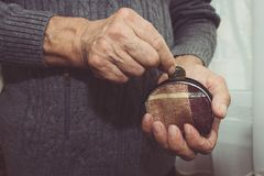 An elderly man puts a coin in an empty wallet. Poverty. In retirement concept. Special toning Royalty Free Stock Photography