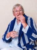 Elderly man putting dentures in stock image