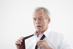 Elderly man putting on his tie Stock Images