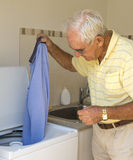 Elderly Man Putting Shirt in Washing Machine. Royalty Free Stock Image