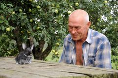 An elderly man with a rabbit. In the country Royalty Free Stock Photos