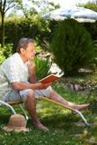 Elderly man reading book Stock Photo