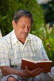 Elderly man reading book. Healthy looking elderly man is his late 70s sitting in garden at home and reading book Stock Photo