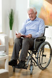 Elderly man reading book at home Stock Images