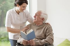 Elderly man reading book. Photo of elderly men reading book and his private nurse Stock Photo
