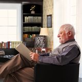 Elderly man reading book at study at home. Elderly man sitting in armchair reading book at study at home Royalty Free Stock Photography