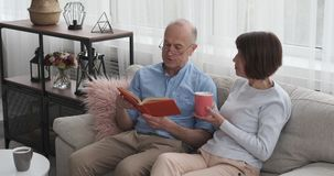 Elderly couple reading book and drinking coffee on sofa stock footage