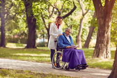 Elderly man reading book in wheelchair with nurse in the park. Elderly men reading book in wheelchair with smiling nurse in the park Stock Photos