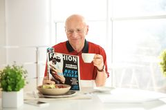 Elderly man reading magazine while having breakfast. At home Royalty Free Stock Photos