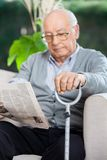 Elderly Man Reading Newspaper At Nursing Home Stock Photo