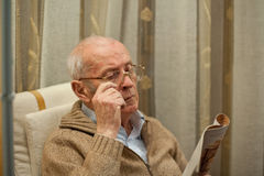 Elderly man reading the newspaper. Settles glasses Stock Image