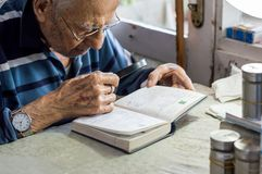 Elderly man reading writings in a notebook with magnifying glass near the window at home. Elderly man reading writings in a notebook with a magnifying glass near royalty free stock images