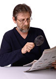 Elderly man reads a newspaper Stock Images