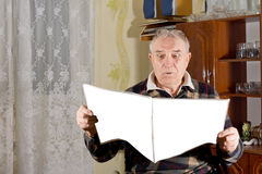 Elderly man ready a juicy bit of news in the paper Stock Photo