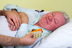 Elderly man receiving medication. Picture of a sick elderly man with his carer holding medication Stock Photos