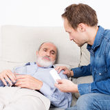 Elderly man receiving some medicine. Sick senior lying in bed with help at his side stock photos