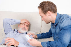 Elderly man receiving some medicine. Sick senior lying in bed with help at his side royalty free stock images