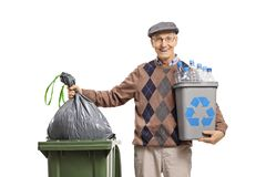 Elderly man with a recycling bin throwing a garbage bag in a trash can. Isolated on white background stock photography
