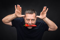 Elderly man with red pepper in his mouth Stock Photos