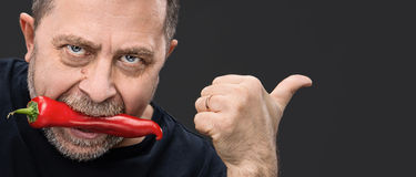 Elderly man with red pepper in his mouth Royalty Free Stock Photos