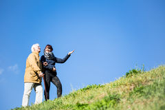 Elderly man relaxing in nature. Picture of elderly men relaxing in nature with helpful carer Stock Photography