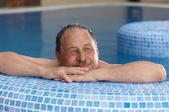 Elderly man relaxing in spa smiling. Elderly man relaxing in spa, smiling, looking away stock photo